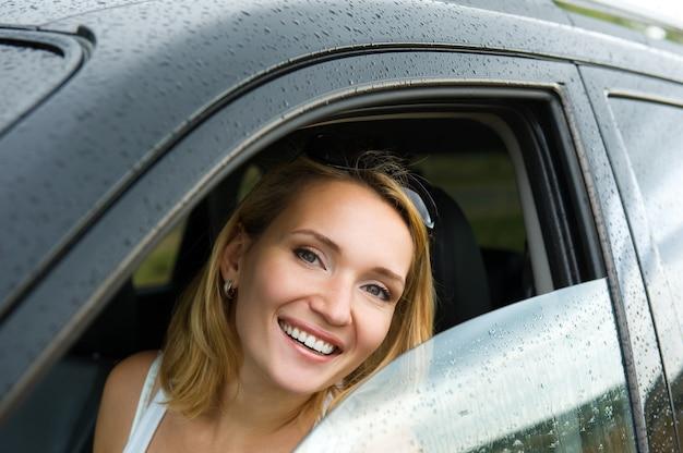 새 차에서 아름 다운 젊은 행복 한 여자의 초상화-야외
