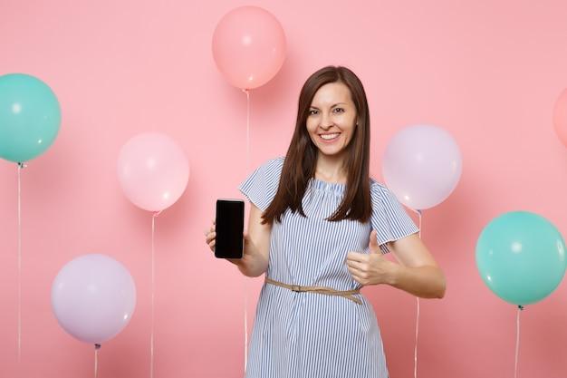 カラフルな気球とピンクの背景に親指を示す空白の空の画面で携帯電話を保持している青いドレスを着て美しい若い幸せな女性の肖像画。誕生日の休日のパーティーのコンセプト。