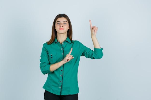 Портрет красивой молодой леди, указывающей вверх в зеленой рубашке и выглядящей уверенно, вид спереди