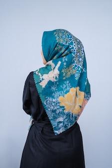 회색 배경에 포즈를 취한 세련된 히잡 스타일의 아름다운 젊은 모델 초상화