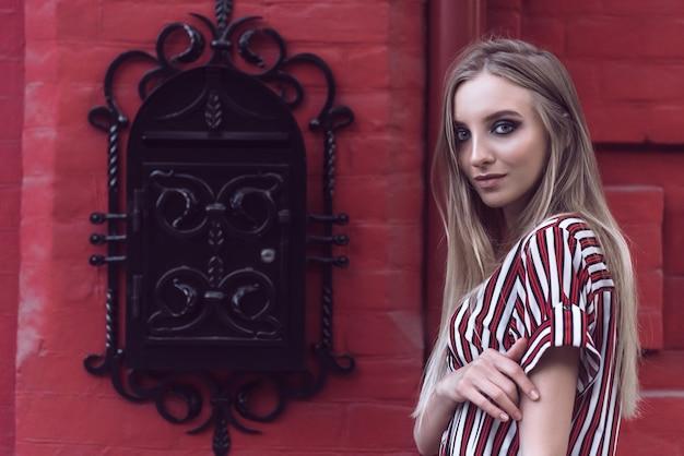 長い髪と背景に赤レンガの壁と明るい化粧の美しい若いモデルの肖像画