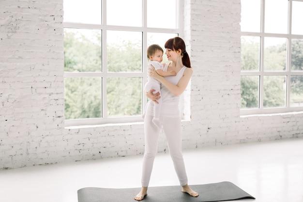 스포츠에서 아름 다운 젊은 엄마의 초상화는 그녀의 매력적인 작은 아기를 들고 검은 요가 매트에 서서 아기를보고 웃