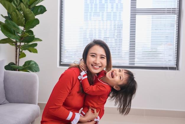 아름 다운 젊은 어머니와 그녀의 딸 포옹, 카메라를 보고 웃 고의 초상화