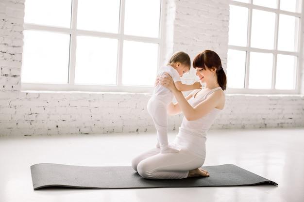 흰색 스포츠에서 아름 다운 젊은 어머니의 초상화는 그녀의 매력적인 작은 여자 아기와 함께 착용