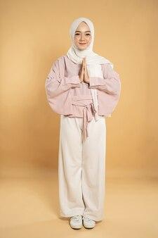 Портрет красивой молодой мусульманской женщины, смотрящей в камеру, вместе показывает жест рукой