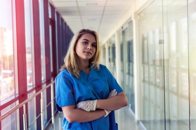 クリニックで青いinofrmの美しい若い看護師の肖像画。健康管理
