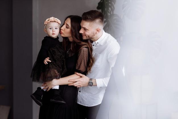 美しい若い親と彼らのかわいい小さな娘の肖像画は抱擁し、室内で笑っています。母の日、父の日、赤ちゃんの日。家族の概念。家族の一見