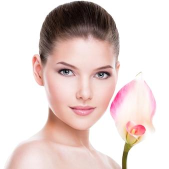健康な肌と顔の近くにピンクの花を持つ美しい若いきれいな女性の肖像画-白で隔離。