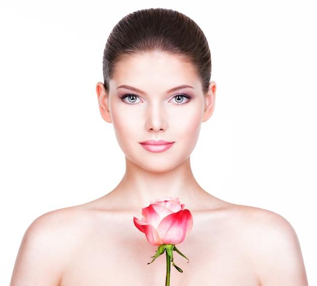健康な肌とピンクのバラの顔の近くに美しい若いきれいな女性の肖像画-白で隔離。