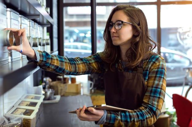커피를 판매하는 소매점에서 재고를 하고 있는 아름다운 젊은 판매원의 초상화.