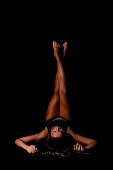 Портрет красивой молодой сексуальной женщины в черной спортивной одежде, тренирующейся в студии