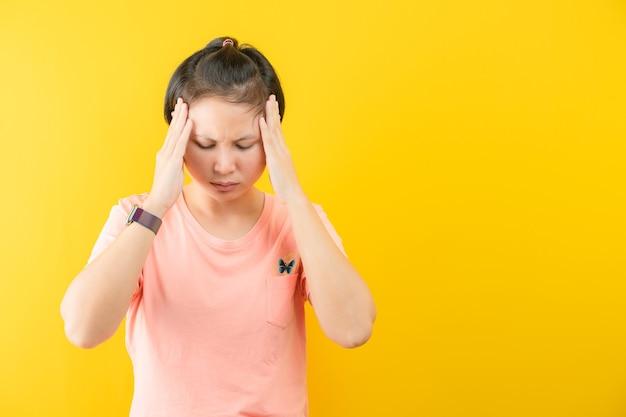 黄色の背景に、ストレスを感じている彼女の寺院に触れて美しい若い短い髪の肖像画