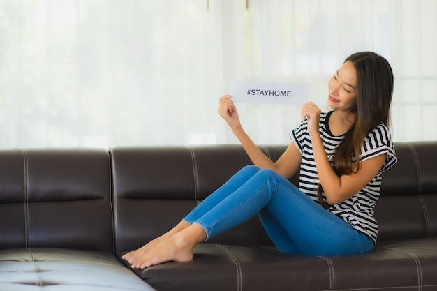 美しい若いの肖像画はソファの上の家のフレーズと紙を示しています