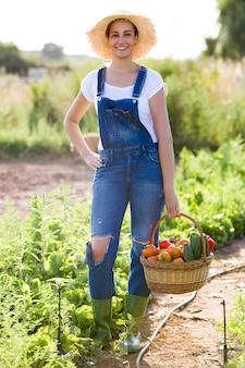 カメラを見ている庭から新鮮な野菜とバスケットを保持している美しい若い笑顔の女性の肖像画。