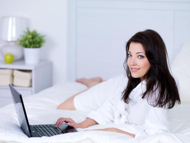 Портрет красивой молодой улыбающейся женщины с ноутбуком утром - в помещении