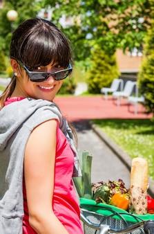 화창한 여름날 선글라스 너머로 자전거를 타고 있는 아름다운 젊은 여성의 초상화