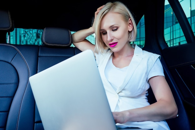 흰색 비즈니스 정장 드레스를 입고 가죽 의자에 앉아 밝은 립스틱을 바른 아름다운 젊고 성공적인 금발 짧은 머리 비즈니스 여성의 초상화는 자동차에 노트북이 있는 증권과 함께 작동합니다.