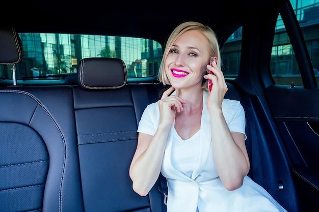 Портрет красивой молодой успешной блондинки короткой стрижки деловой женщины с макияжем в белом платье делового костюма, сидящей на кожаном кресле, работает с ценными бумагами, разговаривает по телефону в машине