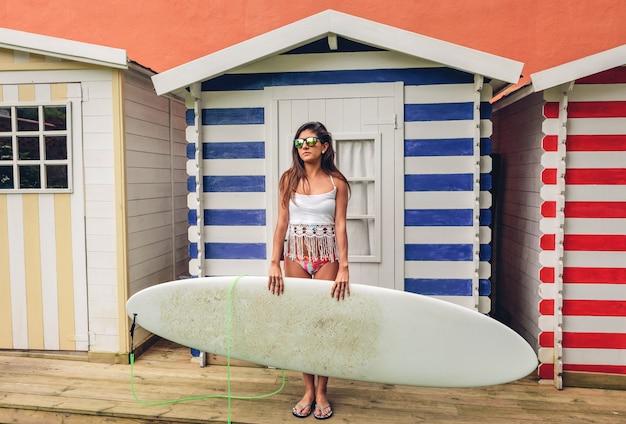 白いトップとビーチの縞模様の小屋の上にサーフボードを保持しているビキニを持つ美しい若いサーファーの女性の肖像画。夏のレジャーのコンセプト。