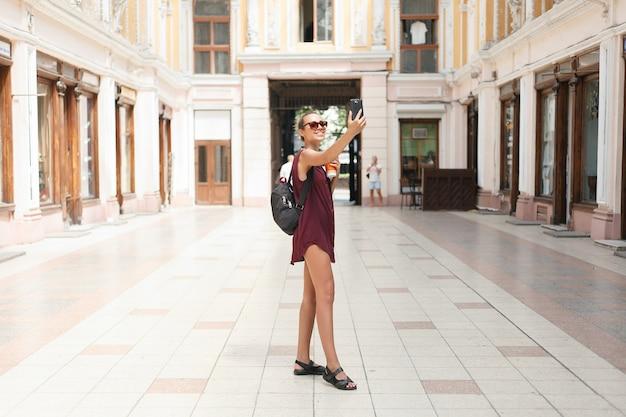 スマートフォンを持って自分の写真を撮り、オンラインでネットワークを構築している美しい若い観光客の女性の肖像画。旅行、テクノロジー、アウトドアライフスタイル。スマートフォンを使用している女性。