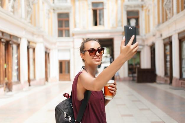 Портрет красивой молодой туристической женщины, держащей смартфон, фотографирующий себя, сети в сети. путешествия, технологии и образ жизни на природе. женщина с помощью смартфона.