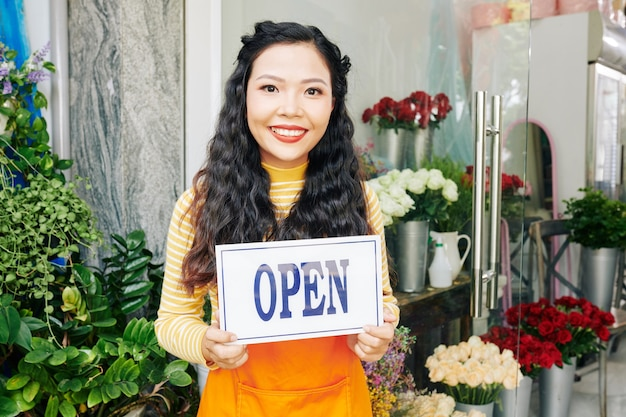 オープンサインとフラワーショップに立っている美しい若いベトナム人女性の肖像画
