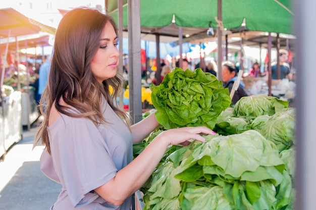 녹색 시장에서 녹색 잎이 많은 야채를 선택하는 아름 다운 젊은 여자의 초상화. 건강 식품 쇼핑의 개념입니다. 녹색 시장에서 야채를 구입하는 젊은 여자.