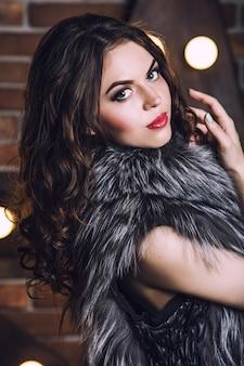 毛皮のジャケットの美しい若い女性のクローズアップの肖像画