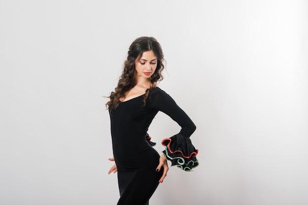 Портрет красивой молодой женщины, танцующей фламенко с веером в студии