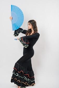 スタジオでファンとフラメンコを踊る美しい若い女性の肖像画 Premium写真