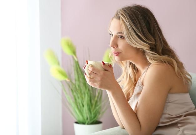 家でコーヒーを飲む美しい若い女性の肖像画