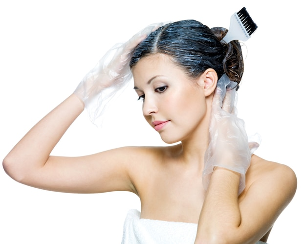 머리카락을 염색하는 아름 다운 젊은 여자의 초상화는 흰색에 고립
