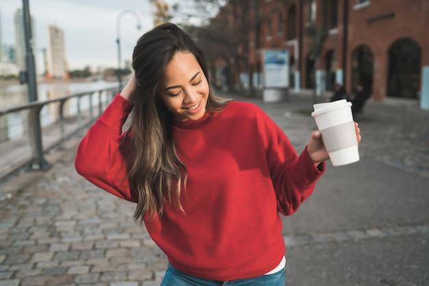 屋外のコーヒーカップを保持している美しい若い女性の肖像画。都市のコンセプト。