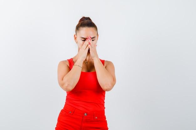 Портрет красивой молодой женщины, держащей руки на лице в красной майке, брюках и выглядящей обнадеживающим видом спереди
