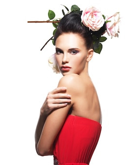 Портрет красивой молодой женщины в красном платье с цветами в волосах - изолированные на белом
