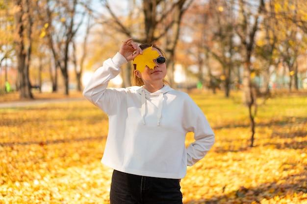 秋の屋外を歩く白いセーターとサングラスの美しい若い女性の肖像画。