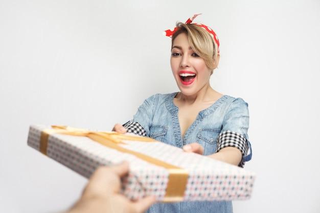 Портрет красивой молодой женщины в повседневной синей джинсовой рубашке с макияжем и красной повязкой на голову, получая подарок со счастливым зубастым улыбающимся лицом. крытая студия выстрел, изолированные на белом фоне.