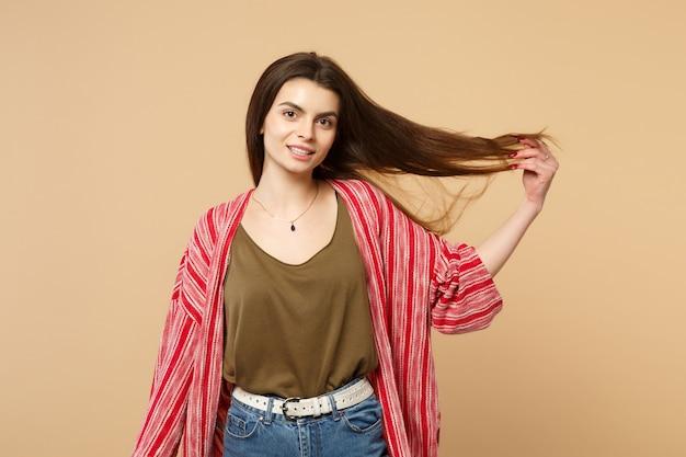 スタジオでパステルベージュの壁の背景に分離された髪を保持しているカメラを探しているカジュアルな服を着た美しい若い女性の肖像画。人々の誠実な感情のライフスタイルの概念。コピースペースをモックアップします。