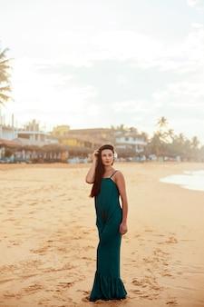 ビーチでドレスを着た美しい若い女性の肖像画。熱帯のビーチでかわいい女の子。自由の概念、休日、ビーチ、空の背景。
