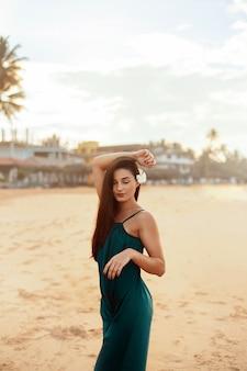 ビーチでドレスを着た美しい若い女性の肖像画。熱帯のビーチでかわいい女の子。自由の概念、休日、ビーチ
