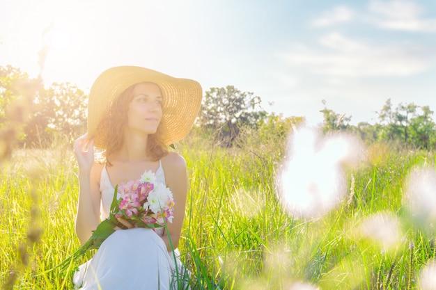 ピンクと白の花の花束を持っておしゃれな帽子の美しい若い女性の肖像画。白いドレスのロマンチックな女の子は、夕暮れ時の広々としたフィールドの緑の芝生に座っています。プロヴァンス風。