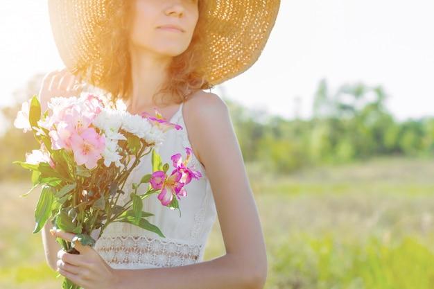 ピンクと白の花の花束を持っておしゃれな帽子の美しい若い女性の肖像画。白いドレスのロマンチックな女の子は歩いて、夕暮れ時の広々としたフィールドで夢を見ています。プロヴァンス風。