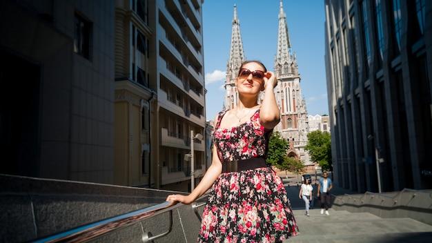 짧은 드레스와 선글라스를 쓴 아름다운 젊은 여성의 초상화는 오래된 가톨릭 성당을 배경으로 도시 거리에서 포즈를 취하고 있습니다