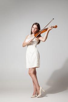 Портрет красивой молодой женщины в белом платье, играющей на скрипке. студия выстрел