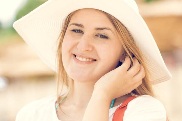 Портрет красивой молодой женщины в белой шляпе позирует на пляже