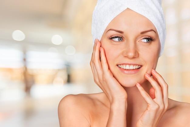 Портрет красивой молодой женщины в белом полотенце на голове на светлом фоне