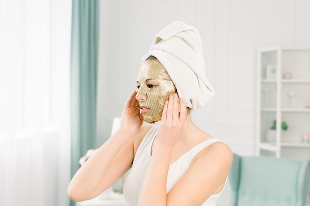 ヌードメイクと顔に化粧紙ゴールドマスクで頭に白いタオルで美しい若い女性の肖像画。