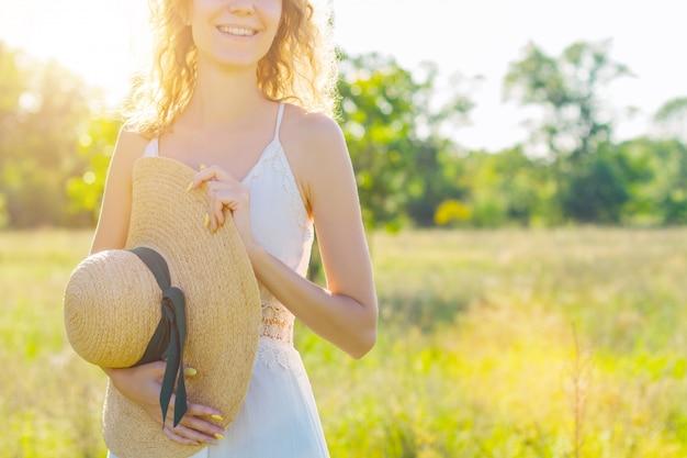美しい若い女性の肖像画は立って、太陽光線でファッショナブルな帽子に笑みを浮かべてください。白いドレスのロマンチックな女の子は歩いて、夕暮れ時の広々としたフィールドで夢を見ています。プロヴァンス風。