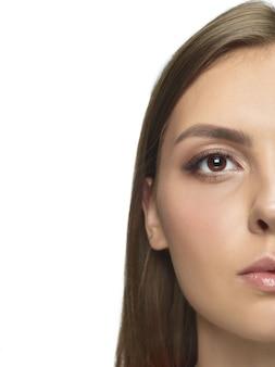 白いスタジオの壁に分離された美しい若い女性の肖像画。