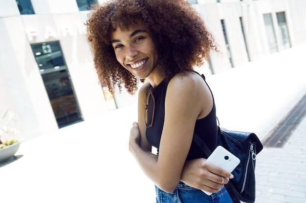 Портрет красивой молодой женщины, смотрящей на камеру на улице.